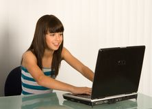 Cute girl with laptop. A cute girl works on her laptop Stock Photos