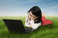 Cute girl with laptop on meadow Stock Photography
