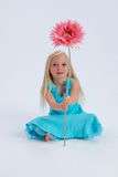 Cute girl with large flower. Cute young blond haired girl with large pink flower; sat on white studio background Royalty Free Stock Photography
