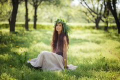 Cute girl laughs with joy outdoors in green wreath. Cute girl laughs with joy outdoors royalty free stock image