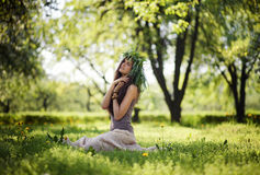 Cute girl laughs with joy outdoors in green wreath. Innocent dream royalty free stock photography