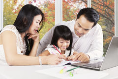 Cute girl learn to write with parents at home Royalty Free Stock Photos