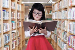 Cute girl in the library aisle. Portrait of beautiful little girl reading a book in the library aisle while wearing glasses Stock Photography