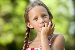 Cute girl licking off chocolate fingers. Royalty Free Stock Photography