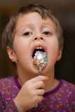 Cute girl licks a spoon Royalty Free Stock Photos