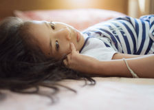 Cute girl lie down on the bed Stock Images