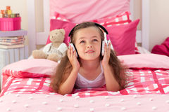 Cute girl listening music in the bedroom Stock Photography