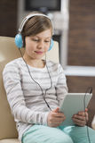 Cute girl listening music while using digital tablet at home Stock Photos