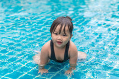 Cute girl or little child playing in swimming pool happily Stock Photos