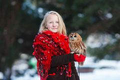 Cute girl with little owl. Cute girl in red scarf standing with little owl in a park royalty free stock photos