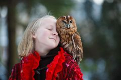 Cute girl with little owl. Cute girl in red scarf standing with little owl in a park stock image