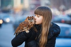 Cute girl with little owl. Cute girl standing with little owl on the street of city royalty free stock photography