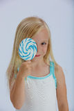 Cute girl with lollipop. Cute young blond girl with large lollipop in front of face; studio background Royalty Free Stock Images