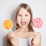 Cute girl and lollipop - difficult choice Royalty Free Stock Photos