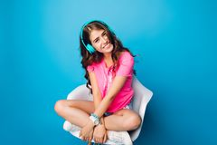 Cute  girl with long curly hair chilling in chair on blue background. She wears shorts, pink T-shirt, white sneakers. Sh.  stock images