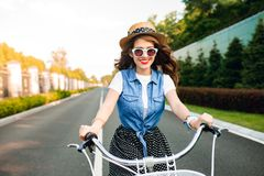 Cute girl with long curly hair in sunglasses driving a bike to camera on road. She wears long skirt, jerkin, hat. Sh.  stock photography