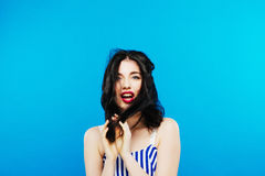Cute Girl with Long Dark Hair Posing in Studio on Blue Background. royalty free stock image