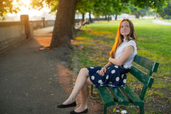 Cute  girl with long golden hair sitting alone on a bench in the Park. Stock Photos