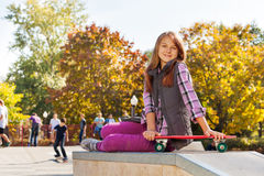 Cute girl with long hair and red skateboard Royalty Free Stock Images