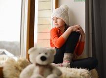 Cute girl with long hair sitting alone near window on  a windowsill Stock Image