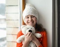 Cute girl with long hair sitting alone near window on  a windowsill Royalty Free Stock Image