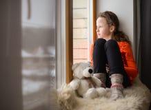 Cute girl with long hair sitting alone near window on a windowsill Royalty Free Stock Photos