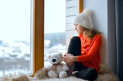 Cute girl with long hair sitting alone near window on  a windowsill Royalty Free Stock Image