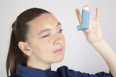 Cute girl looking in asthma inhaler Stock Photography