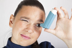 Cute girl looking in asthma inhaler Royalty Free Stock Image