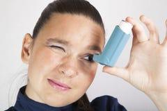 Cute girl looking in asthma inhaler. Smiling cute girl looking in asthma inhaler Royalty Free Stock Image