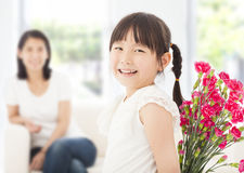 Cute girl looking back and hiding a bouquet of carnations Royalty Free Stock Photos