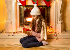 Cute girl looking at Christmas gift at fireplace Royalty Free Stock Photo