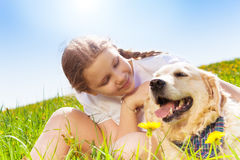 Cute girl looking close at dog and hugging it Stock Images