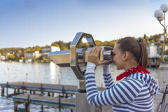 Cute girl looking through a coin operated binoculars Stock Photo
