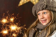 Cute girl looking at festive fire sparks. Close up portrait of cute girl looking at festive fire sparks Stock Photography