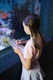 Cute girl looking at fish tank Royalty Free Stock Photo