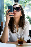 Cute girl looking at her smartphone and making a funny duckface. Stock Image