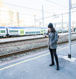 Cute girl looking at her watch and waiting. Cute girl with winter clothes looking at her watch and waiting next to a train station Stock Photos