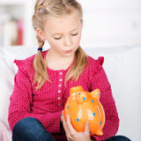 Cute girl looking at piggy bank Stock Photography