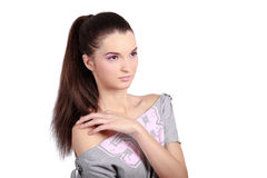 Cute girl looking sideways. Beautiful young woman looking sideways and touching one shoulder. High resolution image taken in studio. Isolated on pure white Royalty Free Stock Image