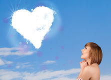 Cute girl looking at white heart cloud on blue sky Stock Images