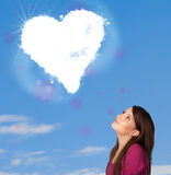 Cute girl looking at white heart cloud on blue sky Royalty Free Stock Photography
