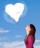 Cute girl looking at white heart cloud on blue sky Stock Photography