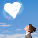 Cute girl looking at white heart cloud on blue sky Stock Photos