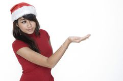 Cute Girl Looking At Your Product. Cute Girl In Santa Hat Looking At royalty free stock photo
