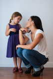 Cute girl looks at her mom with adoring eyes. Cute little four year old girl looks into her mother's eyes with adoration and love. Her mom wears heels and stoops Royalty Free Stock Image