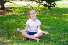Cute girl in lotus pose with sore knee. Photo of cute girl in lotus pose with sore knee Stock Photo