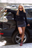 Cute girl and luxury car. Cute girl with sunglasses staying by black luxury car Stock Photos