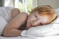 Cute Girl Lying In Bed At Home Stock Photos
