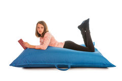 Cute girl lying on blue beanbag sofa for living room or other ro Stock Photos
